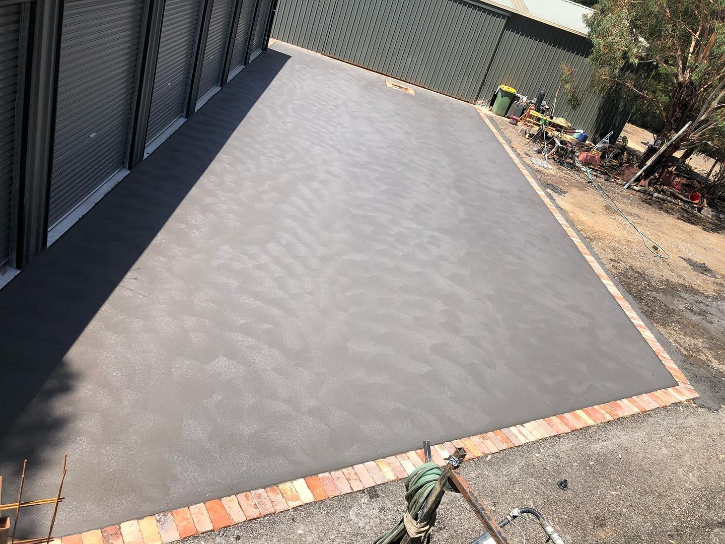 SHed and garage - red brick and charcoal concrete